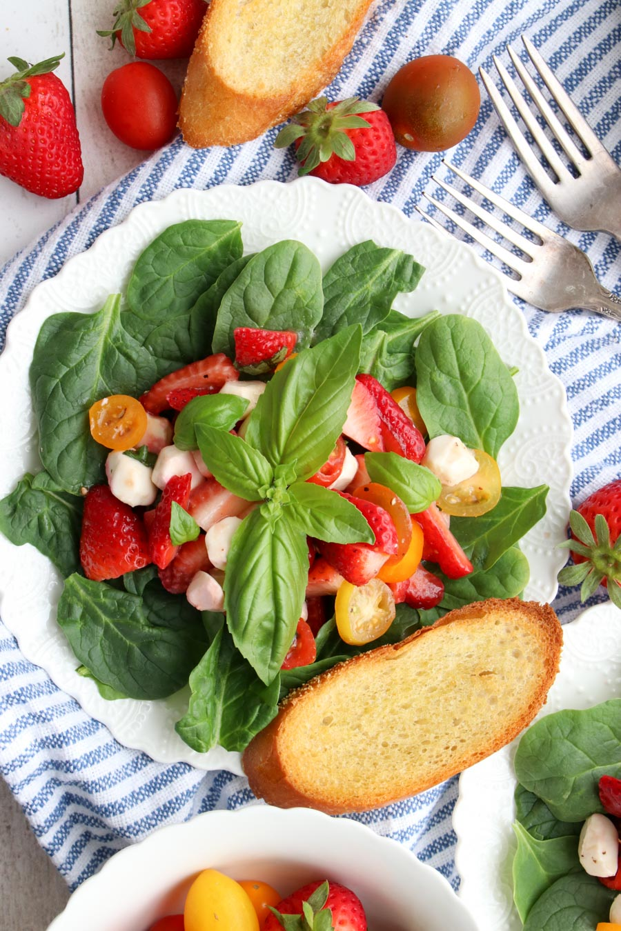 strawberry caprese salad on a white plate with a slice of toasted bread