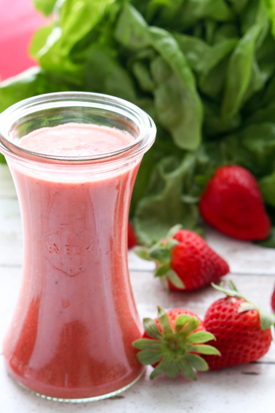bottle of pink strawberry champagne vinaigrette salad greens with lettuce in the background