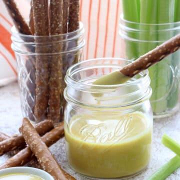 Jar of honey mustard, jar of celery sticks, jar of pretzel sticks