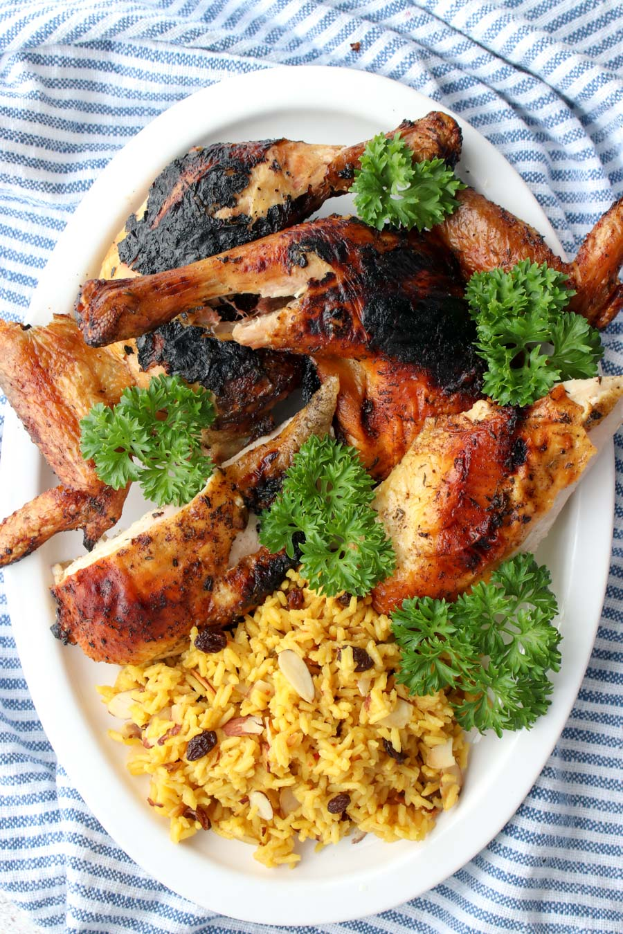 Grilled chicken and yellow rice on a white platter