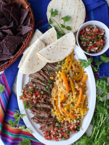 platter of beef fajita with peppers, onions, corn and soft tortillas