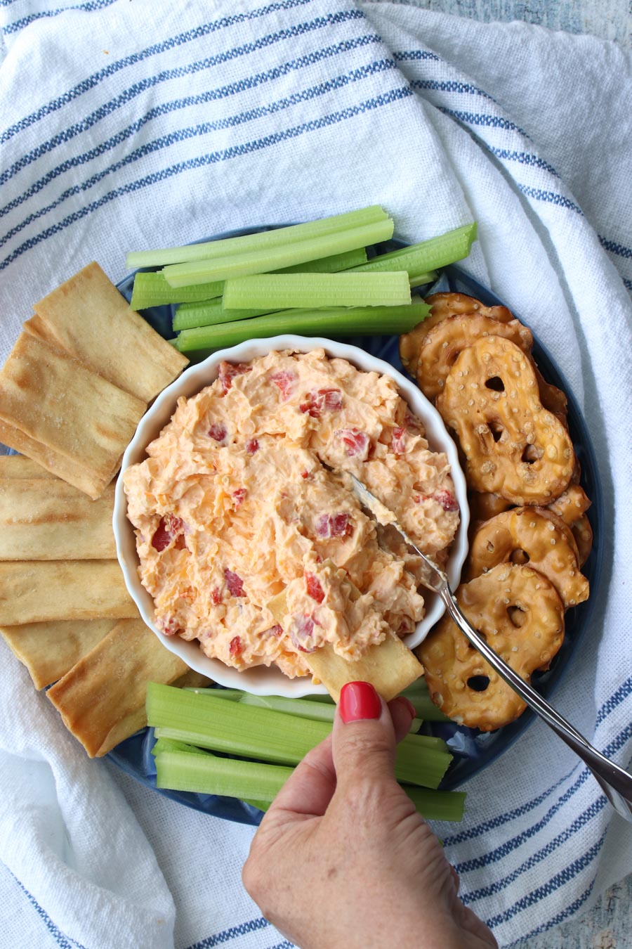 woman's hand dipping cracker into bowl of pimento cheese