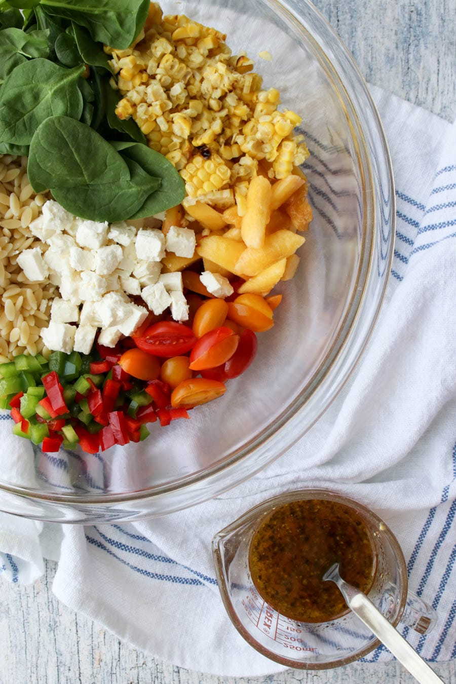 bowl of orzo salad ingredients with dressing on the side
