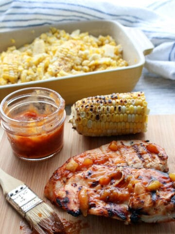 Chicken Breast with Peach BBQ Sauce and a dish of corn in background