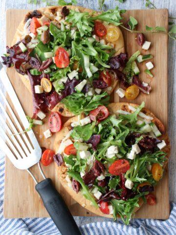 2 Greek Salad Flatbreads on a cutting board with wire spatula
