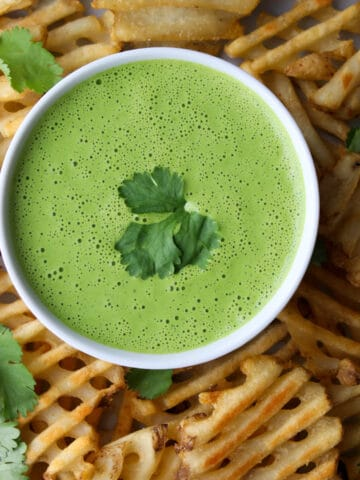 bowl of green cilantro sauce surrounded by waffle fries