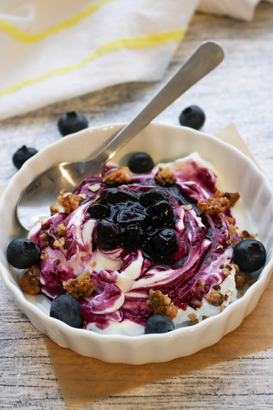 bowl of yogurt covered with blueberry sauce and granola