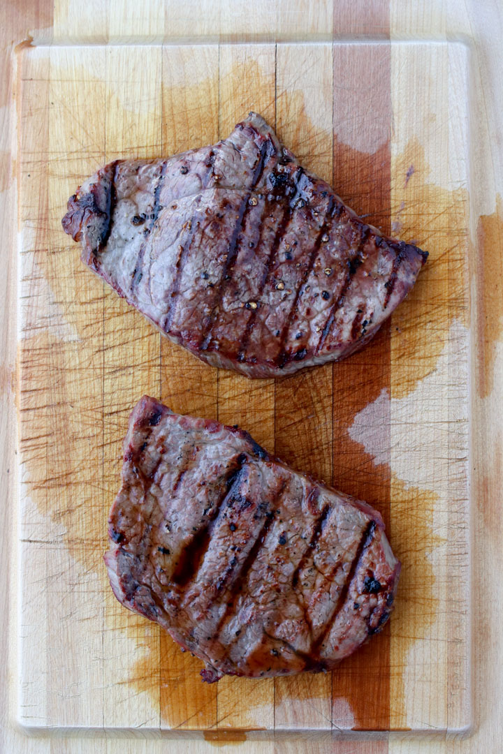two grilled steaks on a large cutting board
