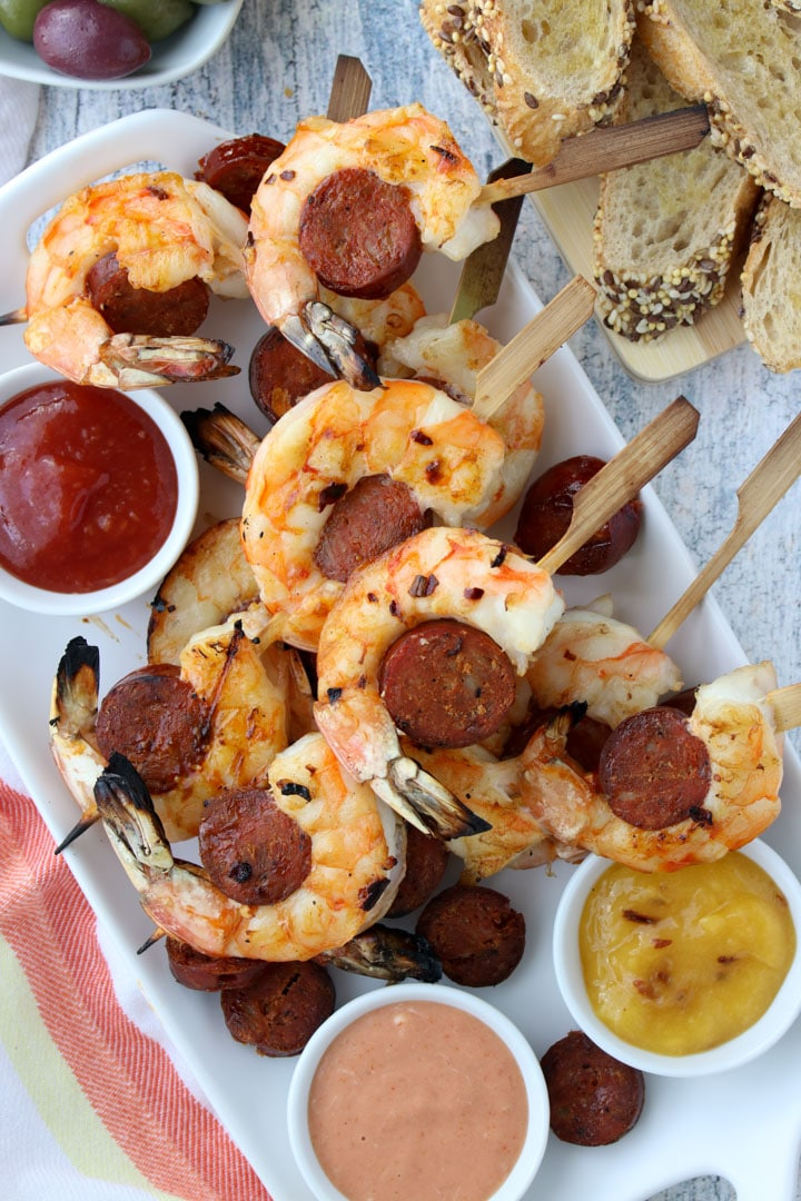 platter of shrimp and chorizo skewers with bread and olives