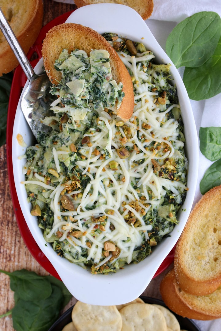 casserole dish with hot spinach dip surrounded by bread and crackers