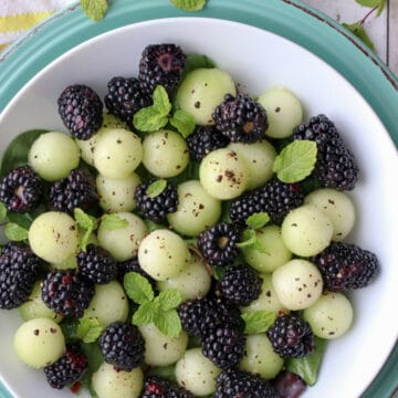 Blackberrys and melon balls in a white dish sprinkled with pepper