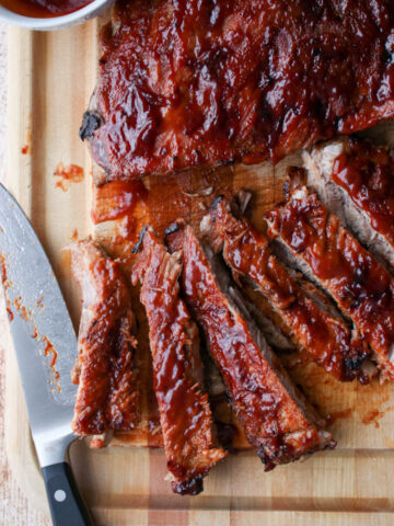bbq ribs on a cutting board with a large knife