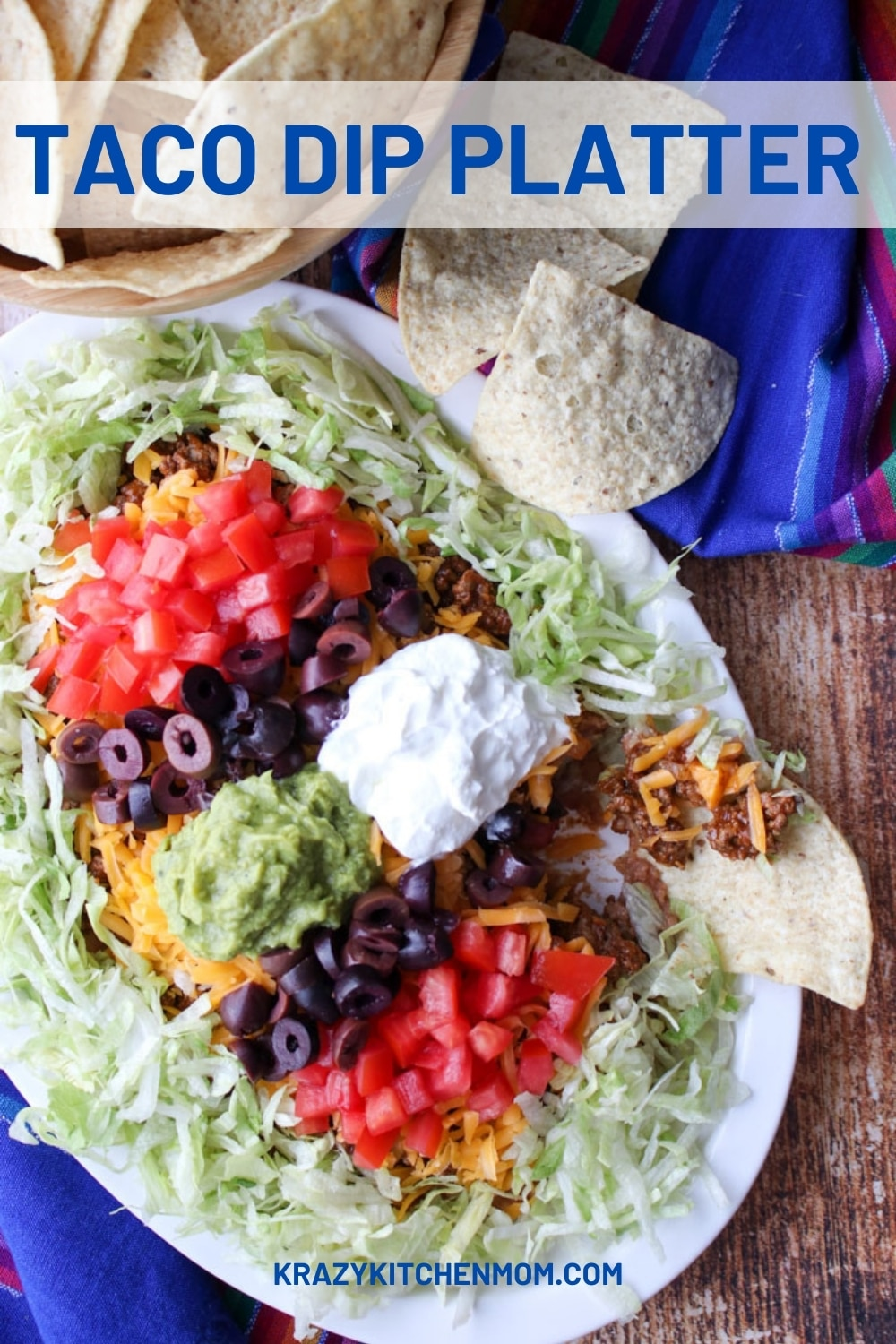 My twist on Mom's layered taco dip plated on a large platter for easy dipping. Layers of beans, taco beef, cheeses, and all the toppings. via @krazykitchenmom