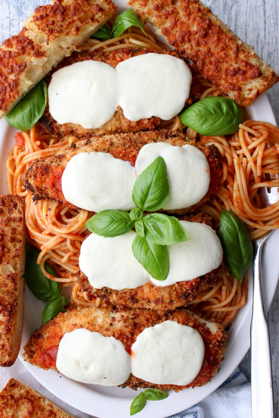 platter of spaghetti and chicken parmesan with garlic bread
