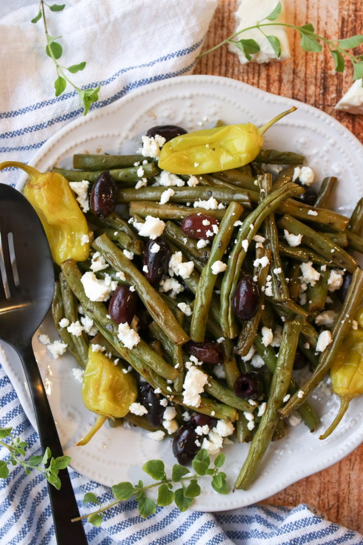 a plate of roasted green beans with olives and peppers