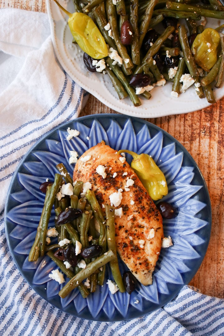 Blue plate with green beans and grilled chicken breast.