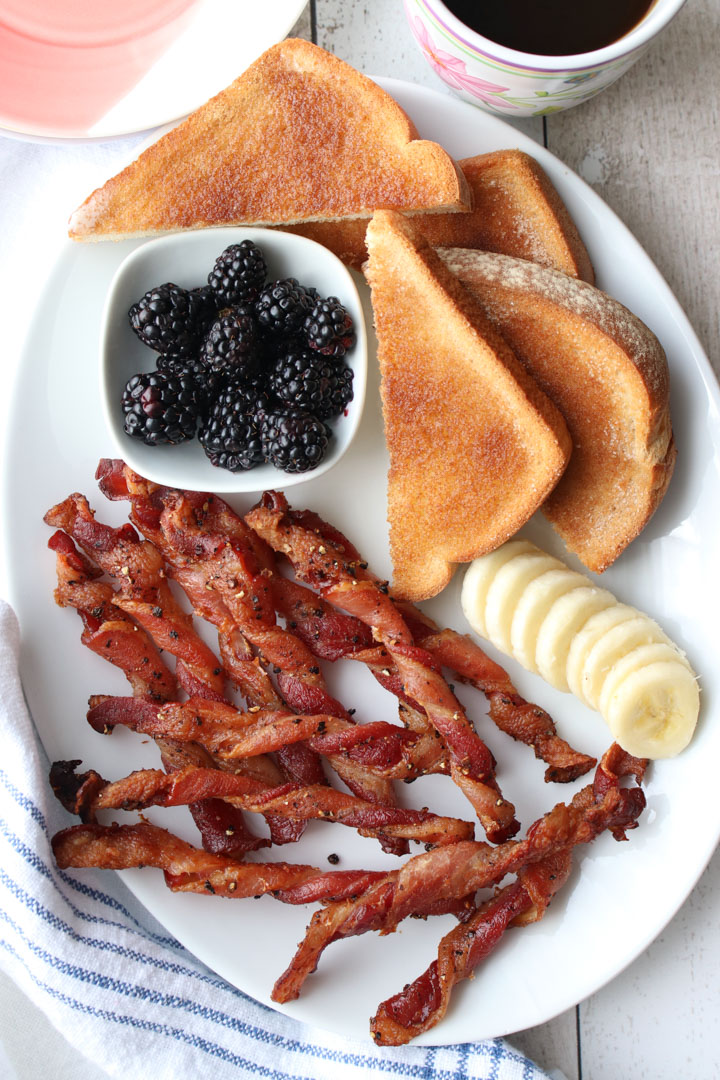 White plate with bacon, banana slices, toast, blackberries